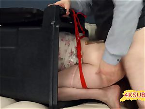 white couch and crimson strap in domination & submission
