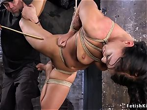 frog-tied in back bend black-haired caned